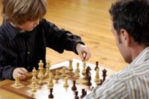 Boy playing chess with his father