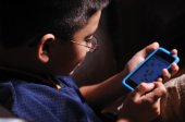 Young boy playing video game on a portable game device